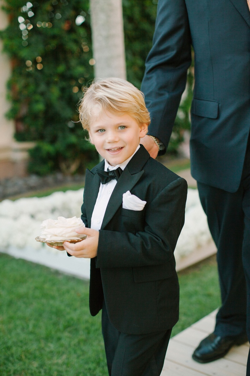 Ring bearer in a black tuxedo and bow tie holds white rose