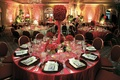 Reception table with red tablecloth and red rose flower arrangements