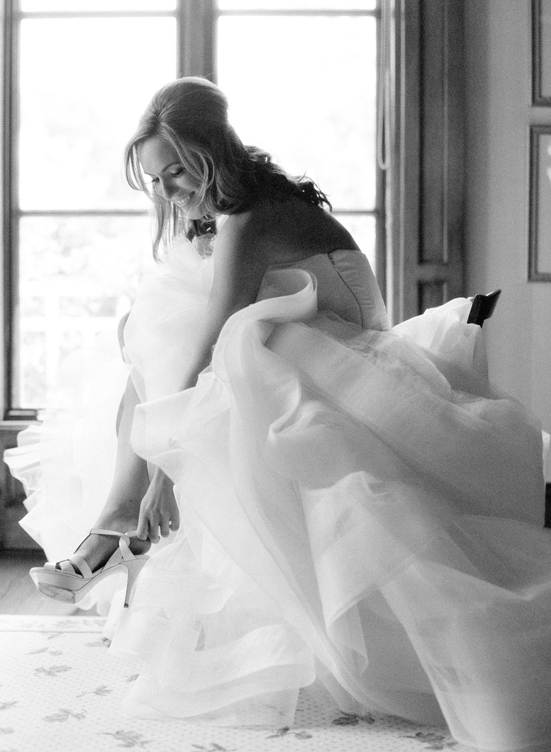 Black and white photo of bride in Vera Wang wedding dress putting on high heel shoes