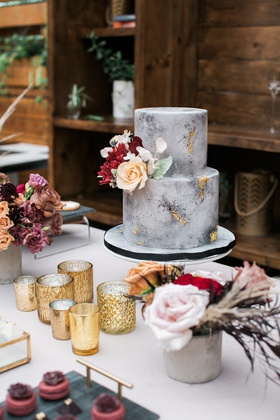 small two-tier grey marble cake made to look like concrete with gold foil and fresh flowers