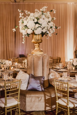 wedding reception ballroom velvet banquette pillows gold chiavari chairs white hydrangeas cushions