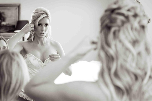 Black and white photo of a bride putting on chandelier earrings