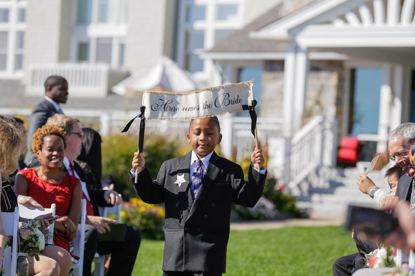 "Ring bearer holding ""Here Comes the Bride"" sign"