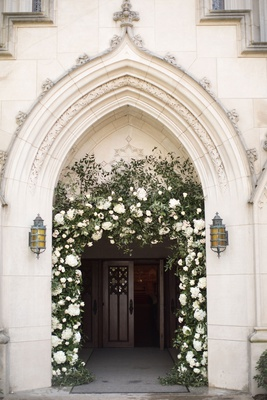 church ceremony entrance archway with greenery white flowers decorating arch