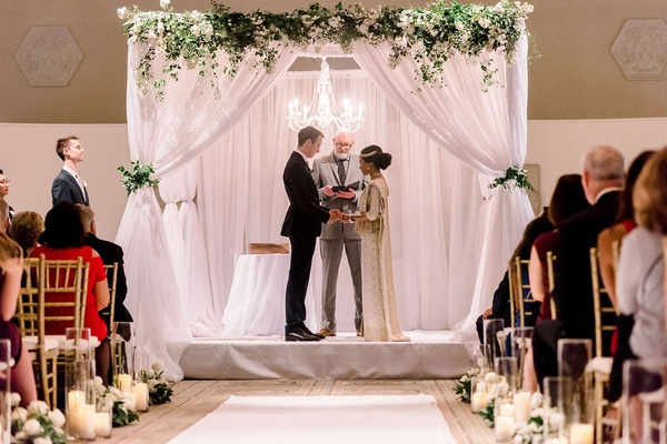 interfaith ceremony with south asian bride, ceremony structure with white drapery and greenery