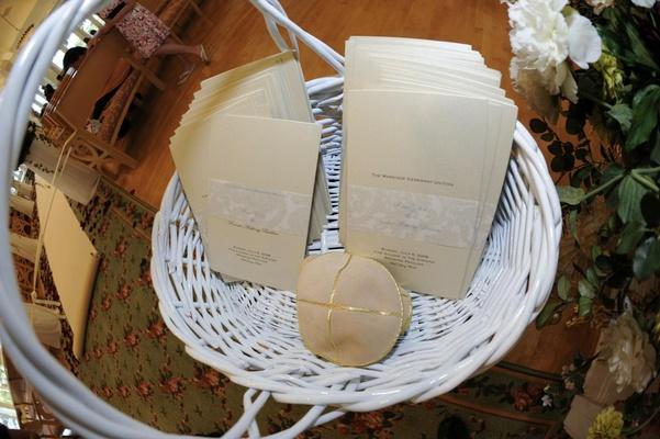 White basket holding ivory wedding programs
