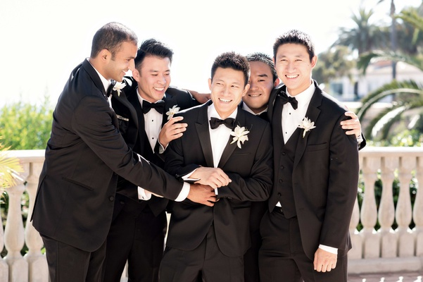 playful moment groom groomsmen classic wedding attire white boutonniere funny poses