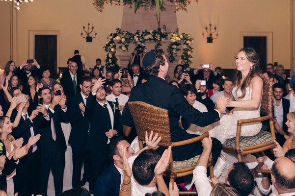 jewish wedding horah dance bride and groom lifted in chairs at reception