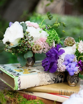 Outdoor wedding reception table with white and purple flowers in small vases on books