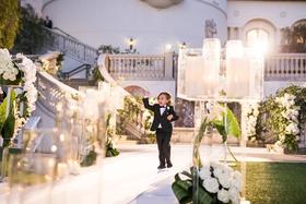 Wedding ceremony evening jewish custom ring bearer in tuxedo walking down white aisle candles lights