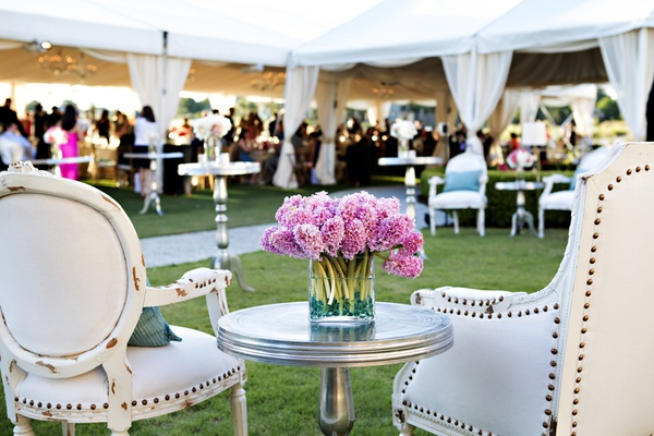 Pink flower arrangement at outdoor wedding lounge area
