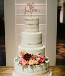 semi naked wedding cake on wood table with pink orange rose dahlia flowers greenery laser cut topper