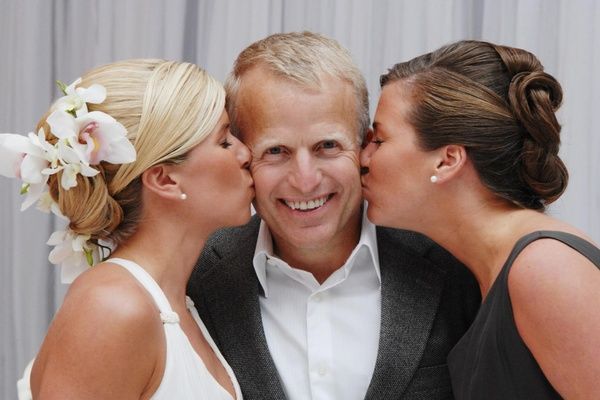 Bride and sister kiss father of bride on cheek