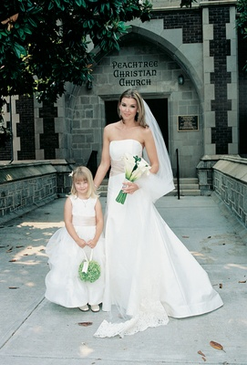 Woman in wedding dress with young girl