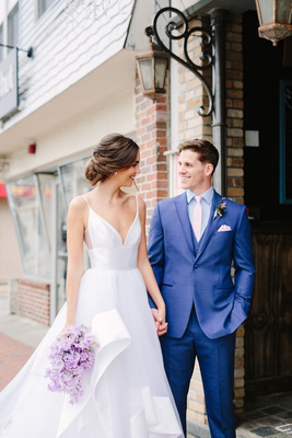 Bride in hayley paige wedding dress layered skirt, bouquet of lavender stock, groom in blue suit
