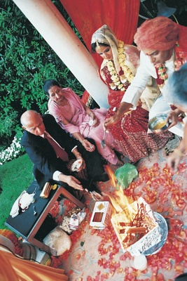 Bride, groom, and parents offer items into fire