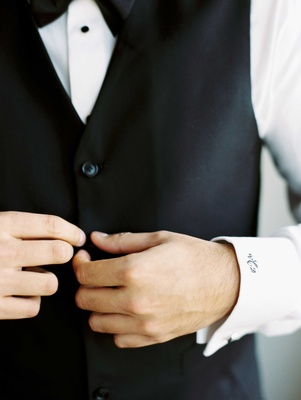 Groom buttoning up black tuxedo vest with black three letter monogram on white shirt cuff