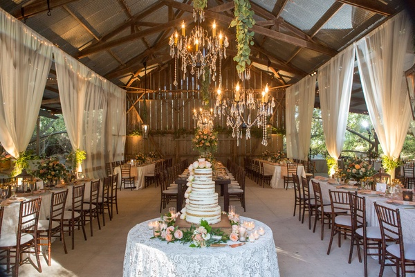 Barn wedding reception with elegant design white drapery linens naked cake chandelier greenery