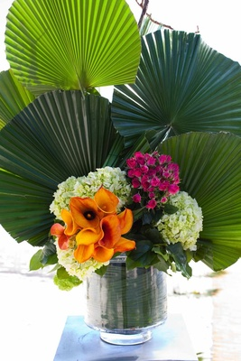 Fan palm fronds in glass vase with calla lily flowers