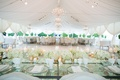 Wedding reception table glass tabletop crystals white glassware flowers gold candle votives