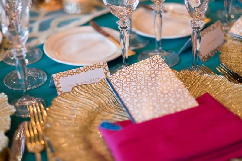 turquoise gold pink tablescape at place setting leafed charger plate with geometric menus