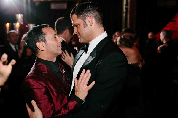 Matthew Christopher, couture wedding gown designer, in a black tuxedo dances with his groom