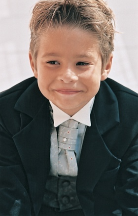 young ring bearer wears blue tie and vest