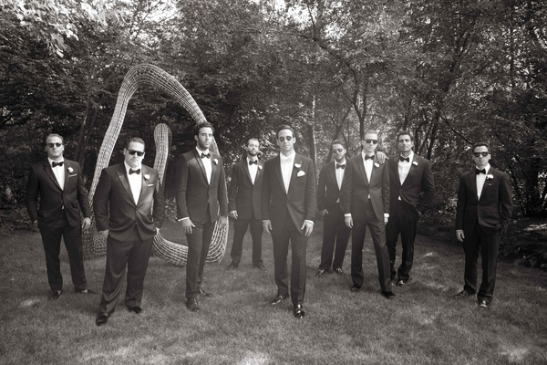 Black and white photo of groom and groomsmen in tuxedos with black and white bow ties