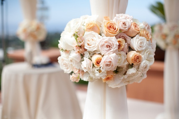 Orange and pink roses around chuppah pillars