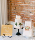 a dessert table with a white copper motif in the table linen, signage and cake elements themselves