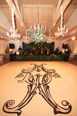 dance floor with large, ornate monogram in black, chandeliers above