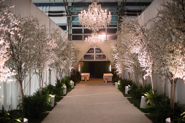 Wedding reception entrance to dinner space cherry blossom trees and greenery chandeliers drapery
