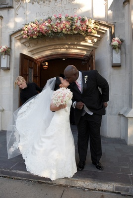 bride and groom kiss after ceremony outside church