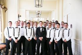 Groom in tuxedo with groomsmen in black pants white shirts black bow ties and suspenders