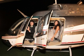 Groom and bride in Monique Lhuillier wedding dress inside helicopter for wedding reception exit