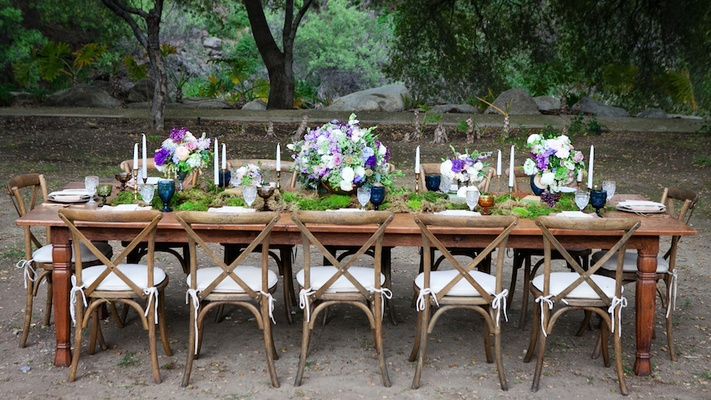 Outdoor wedding reception with wood table, chairs, moss runner, pink, purple, white flowers