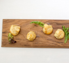 Cheese puffs, lettuce leaves on a wood platter for outdoor wedding shower