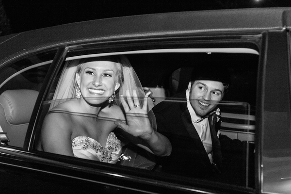 Black and white photo of couple in sedan leaving reception