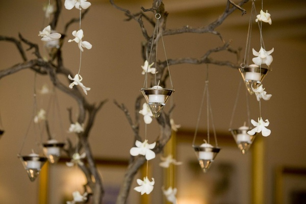 White flowers and candles hanging from tree branches