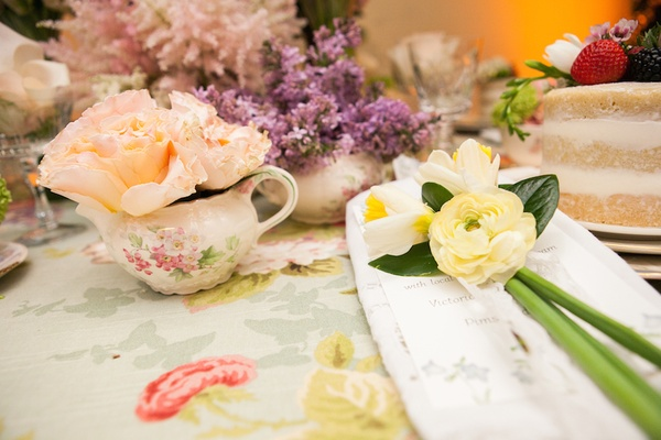Ranunculus flower arrangement on top of menu card at afternoon tea