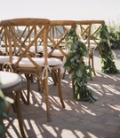 Arrangement of eucalyptus leaves on wooden wedding ceremony chairs