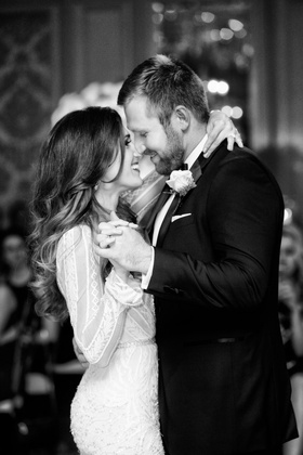 Black and white photo of bride in Inbal Dror wedding dress with groom in tuxedo touching noses