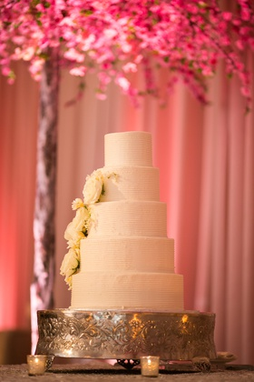wedding cake with white buttercream in textured lined pattern, white roses and peonies