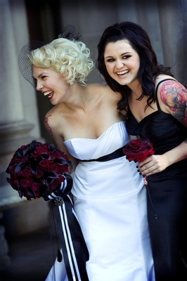 Bride in a strapless Alvina Valenta gown and black sash with bridesmaid in a black dress