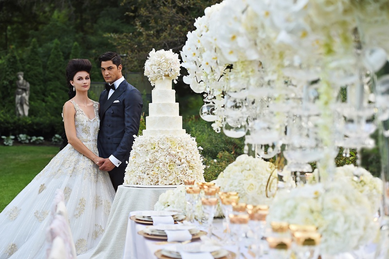 bride in ines di santo julia, groom in midnight blue tuxedo, look upon large cake, decorated table