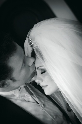 Black and white photo of groom kissing bride