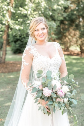Bride in lace illusion long sleeve wedding dress holding natural rustic bouquet greenery pink white