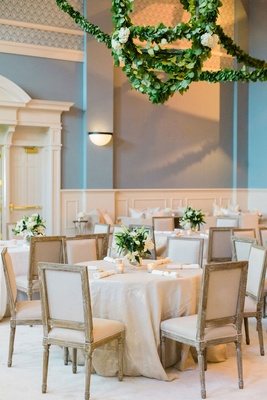 Wedding reception blue walls garlands greenery on lantern chandelier over tables with beige linens