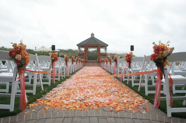 Outdoor wedding ceremony decorated with pink, orange, and yellow flowers