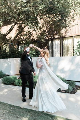 bride in jinza couture bridal gown, groom twirls bride during first look